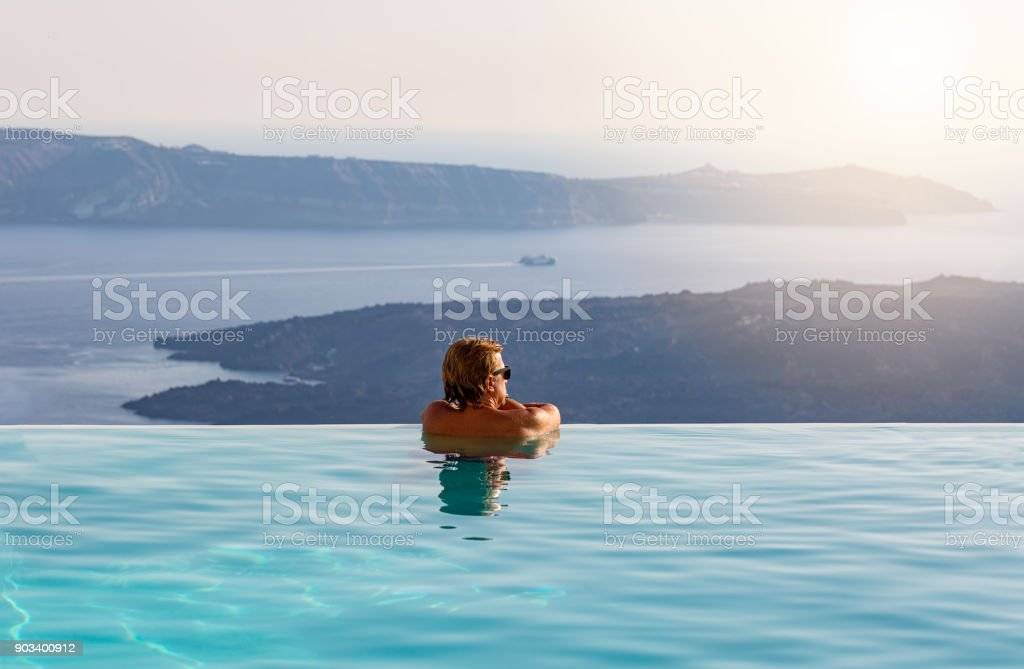Man relaxing in infinity swimming pool, looking at the sea view stock photo