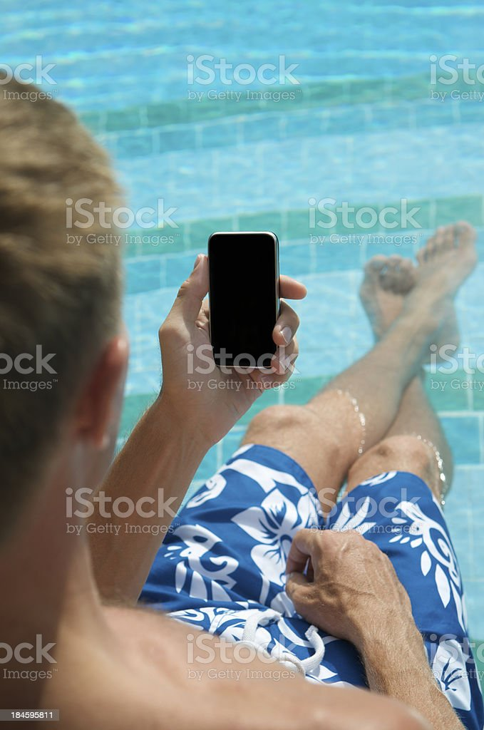 Man Relaxing in Swimming Pool with Smartphone Mobile Phone royalty-free stock photo