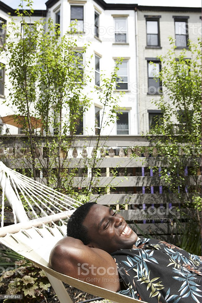 Uomo rilassante su un'amaca nel giardino urbano foto stock royalty-free