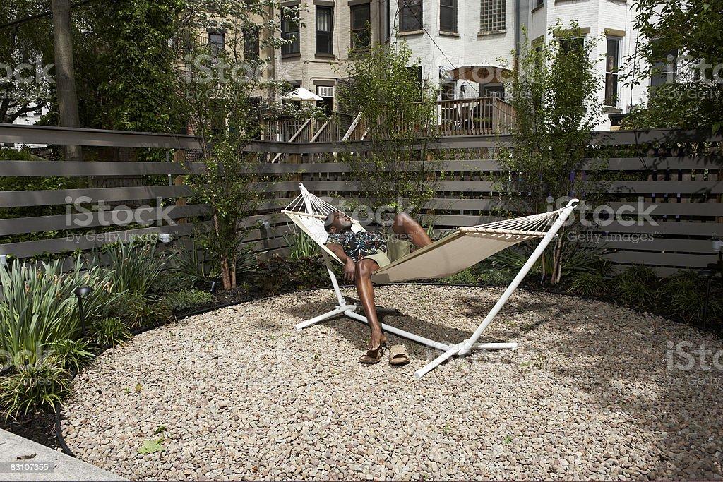 Man relaxing in urban backyard hammock royalty free stockfoto