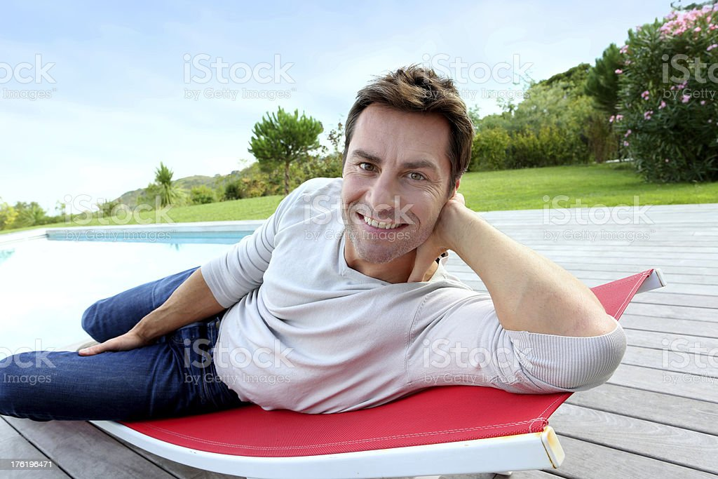 Man relaxing near pool on sunny day royalty-free stock photo