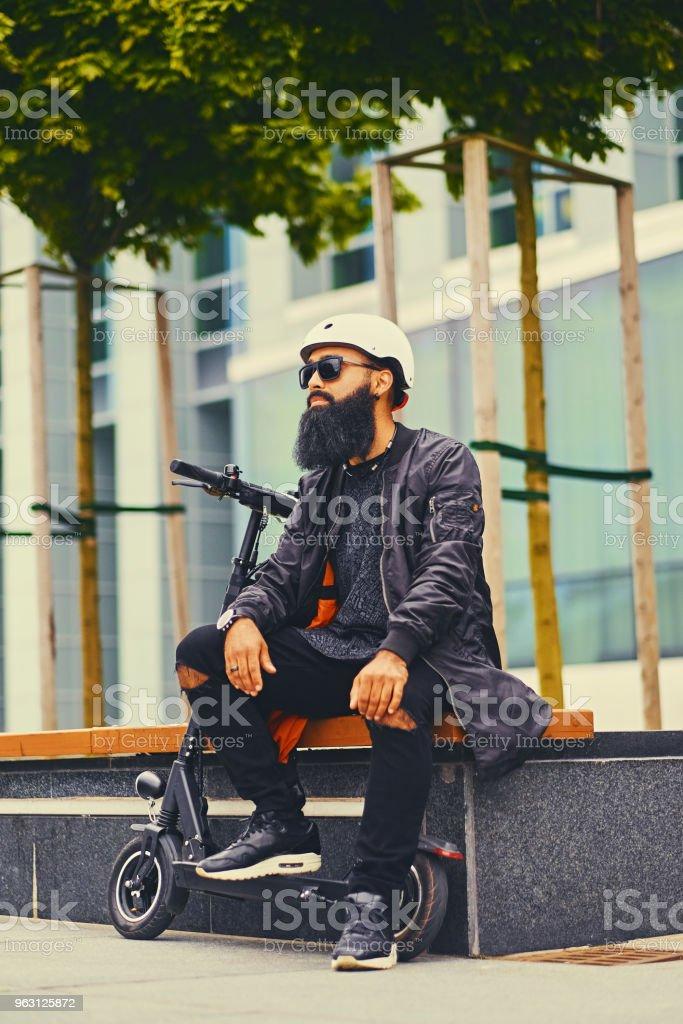 En man som är avkopplande på en bänk efter ridning av elektrisk skoter. - Royaltyfri Ansiktshår Bildbanksbilder