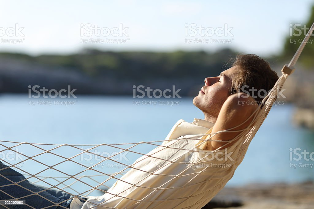 Man relaxing on a hammock in the beach - foto de acervo