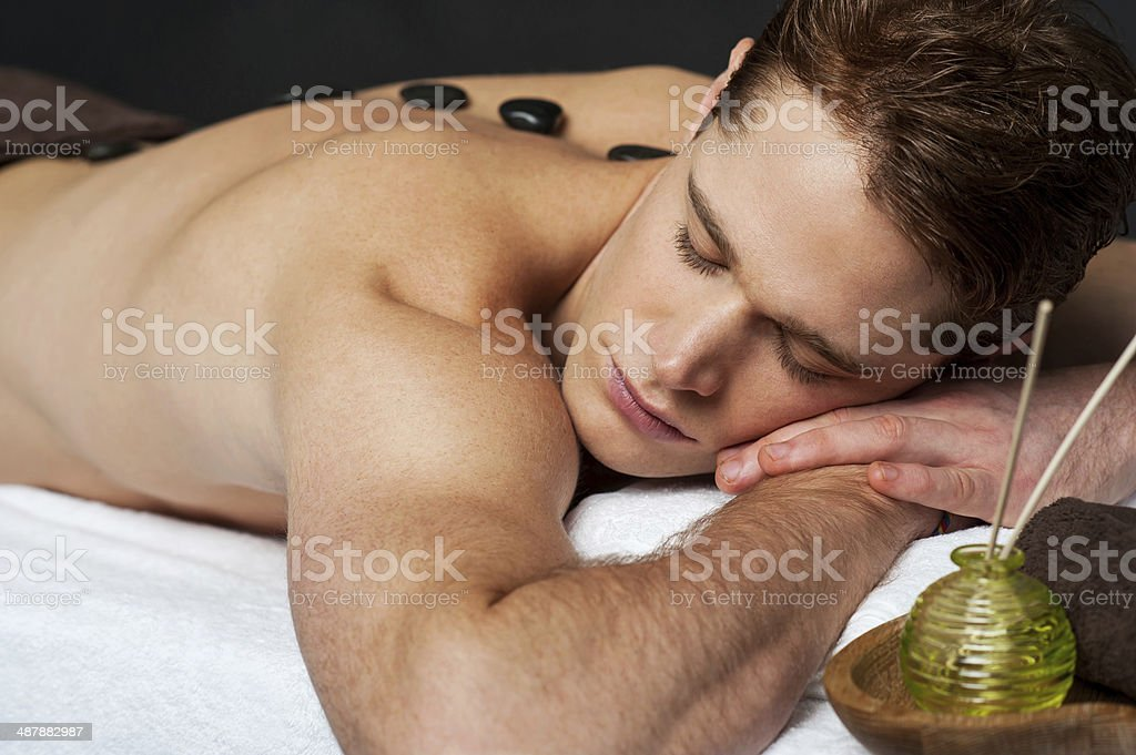 Man relaxing on a massage bed with hot stones stock photo