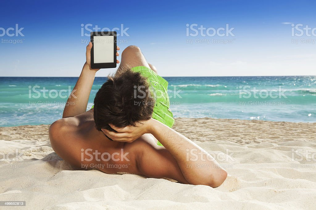 Man relaxing on beach reading e-book Man relaxing on beach laying on sand and reading e-book on white sand background Adult Stock Photo