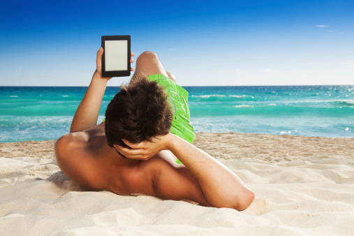 Man Relaxing On Beach Reading Ebook Stock Photo - Download Image Now