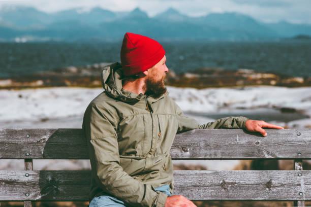 Mann auf Bank genießen Sie Meer und Berge Landschaft Norwegen-Urlaub-Reisen-Lifestyle-Konzept. Reisenden sitzen allein tragen Mode rote Hut denken, Herbstsaison – Foto