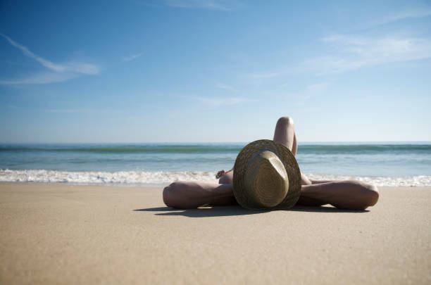 Man Relaxing on Deserted Beach Wearing Hat stock photo