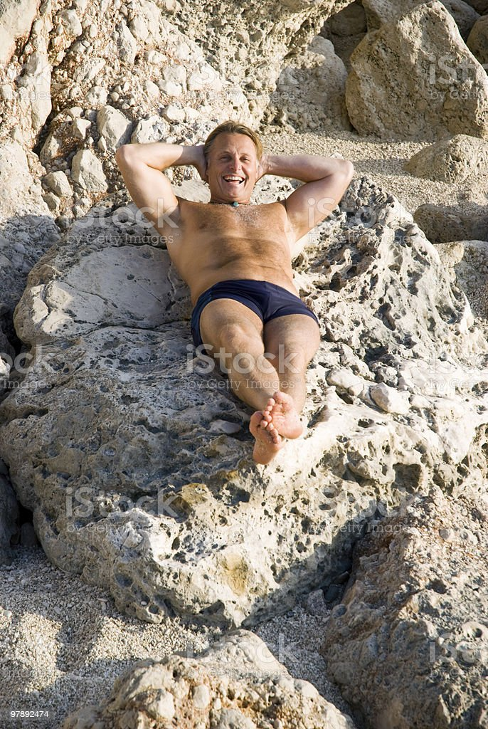 Man relaxing on rocks. royalty-free stock photo