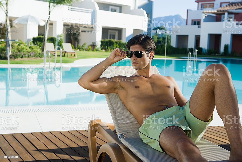 Man relaxing on sunlouger by poolside royalty-free stock photo