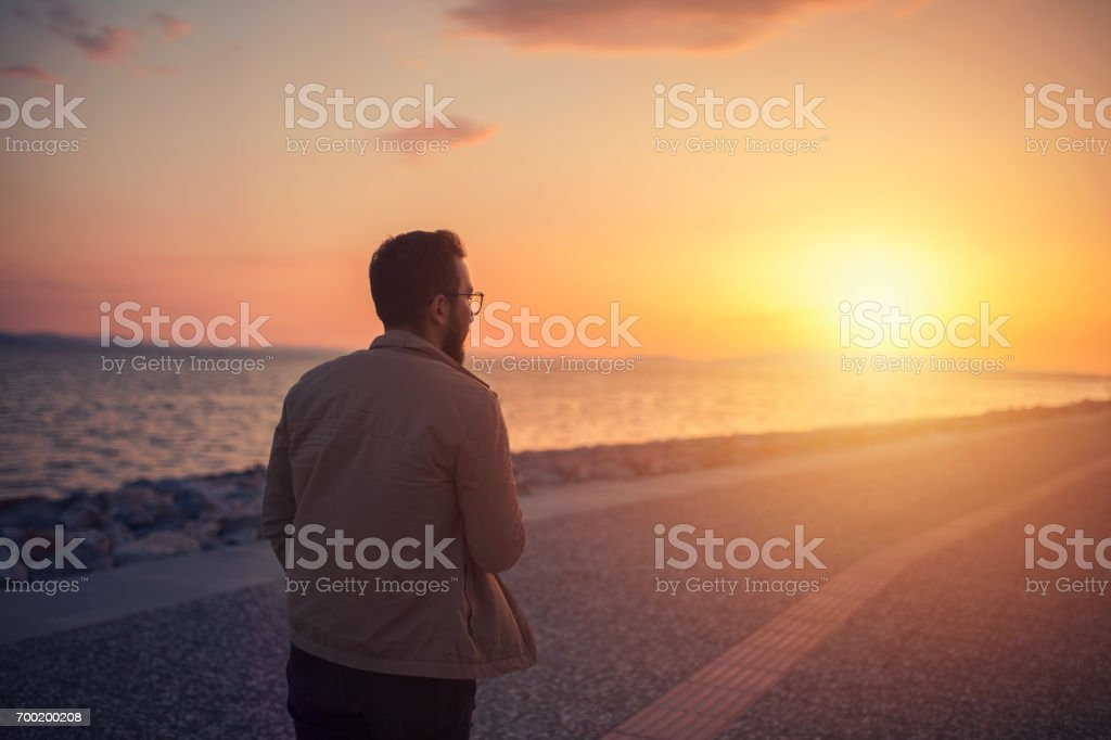 Man relaxing on the beach at sunset. stock photo