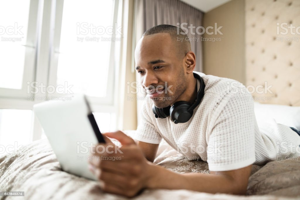 man relaxing on the bed listening music stock photo