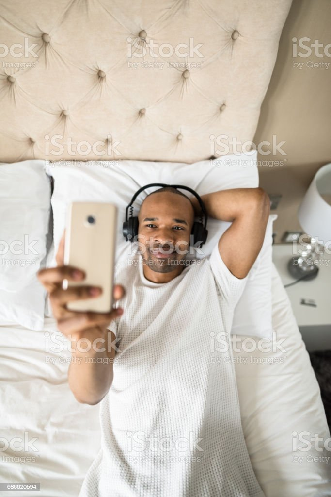man relaxing on the bedroom with headphone royalty-free stock photo
