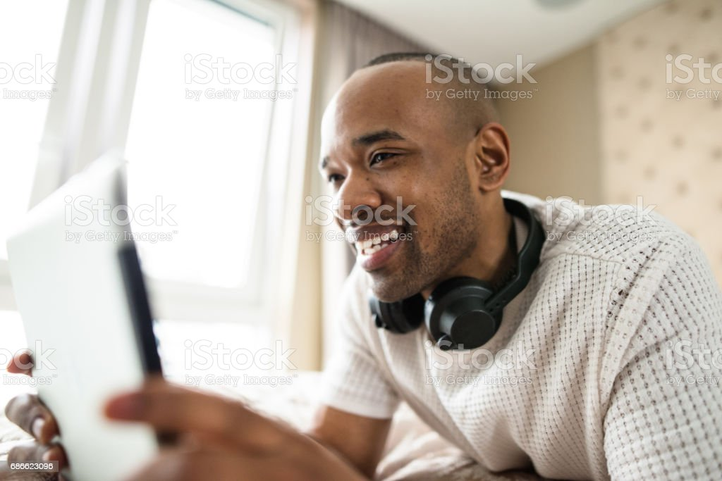 man relaxing on the bedroomand using the tablet royalty-free stock photo