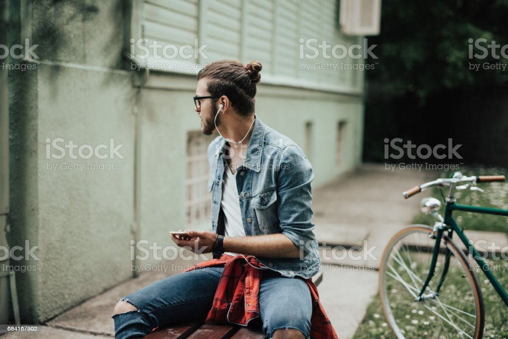 Man relaxing on the bench listening to his favorite podcast foto stock royalty-free