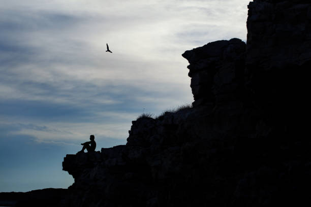 man relaxing on the cliff - tamara dragovic stock photos and pictures