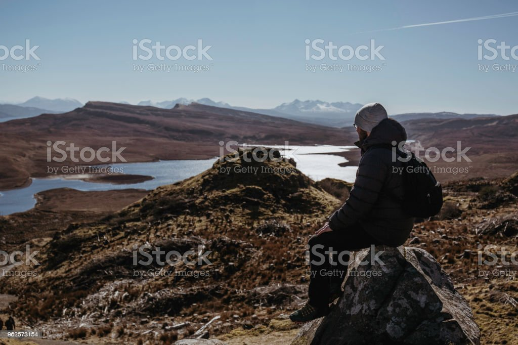 Man relaxing on top of the Old Man of Storr walk on Isle of Skye, Scotalnd, sitting on a stone. stock photo