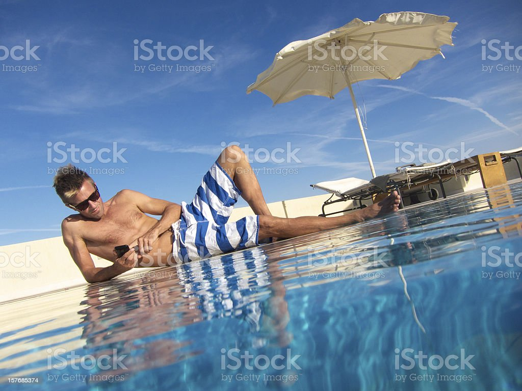 Man Relaxing Poolside Texting on Smartphone in Striped Shorts royalty-free stock photo