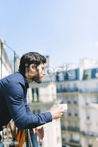 Young good-looking well-dressed man is enjoying the sunshine outside his apartment in a sunlit balcony surrounded by other apartment houses. The image is scenic and has lot of clean space. The man seems relaxed and thoughtful. Copy space available. Made in Paris, France.