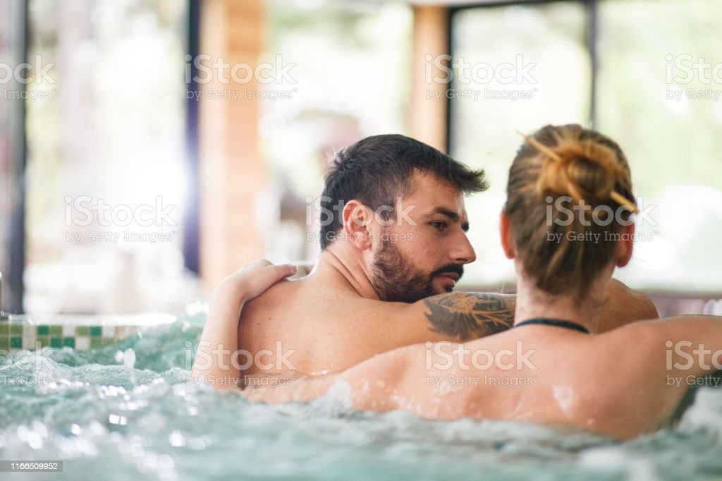 Caucasian man with a tattoo and his girlfriend are relaxing in a...