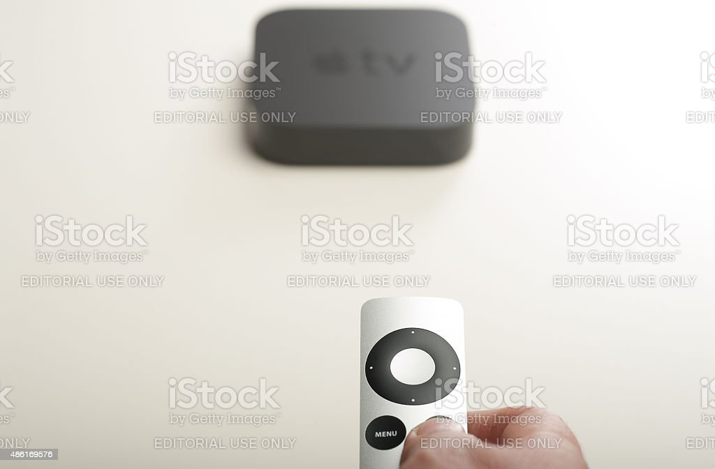 Man remotely controlling his Apple TV device stock photo