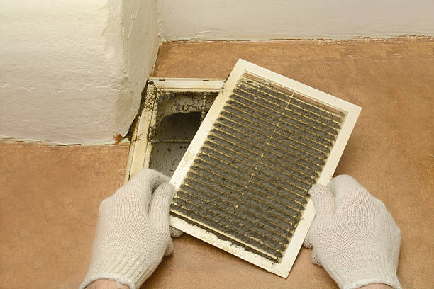 man removes dust ventilation grilles stock photo