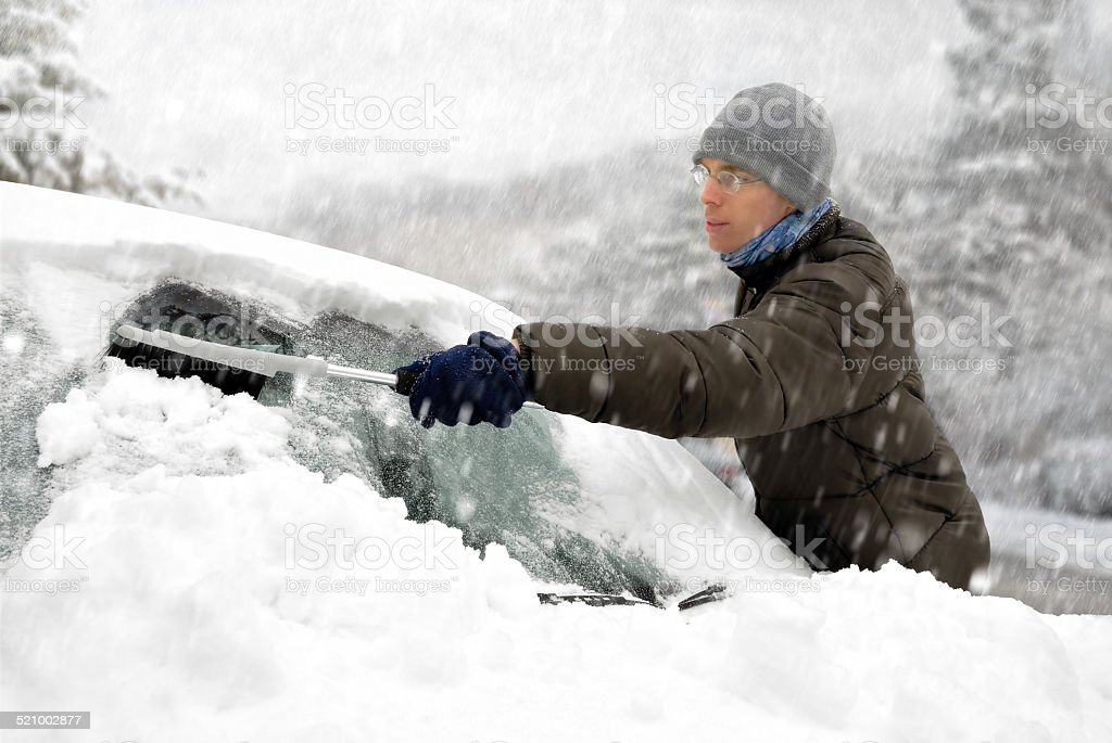Man removes snow from his car stock photo
