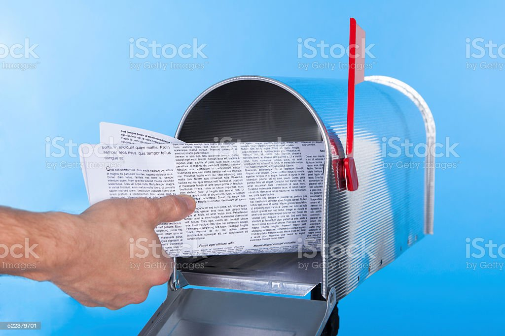Man removing a newspaper from his mailbox stock photo
