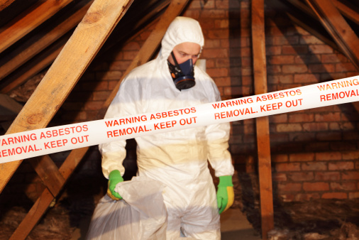 A worker wearing protective clothing while clearing the hazardous substance,asbestos,from an old attic.