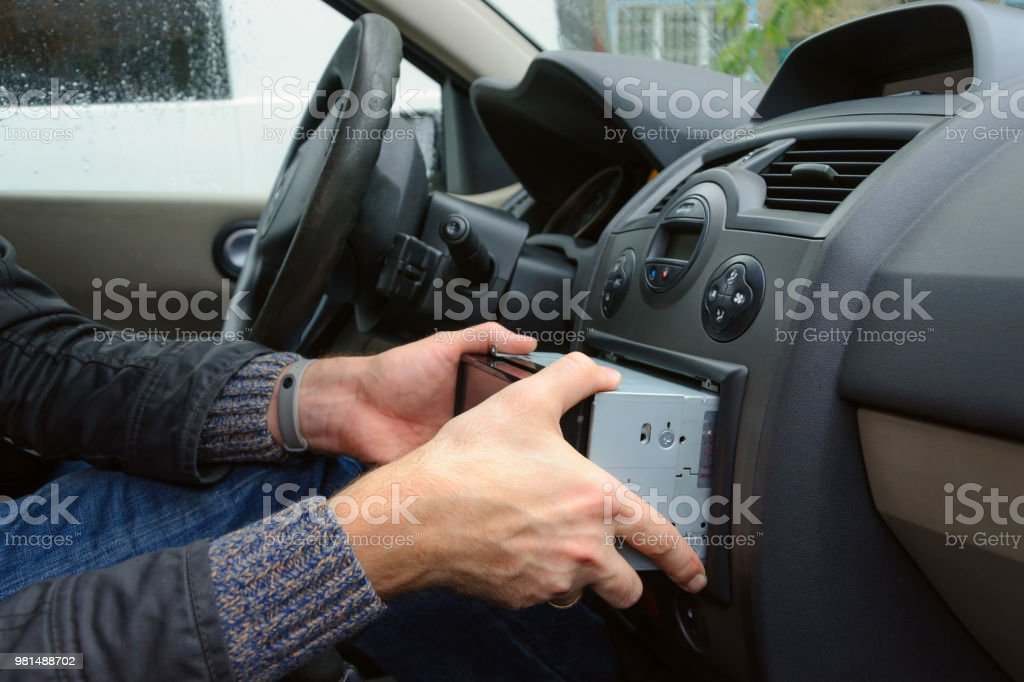 Man Removing Audio System From Car Dashboard Stock Photo