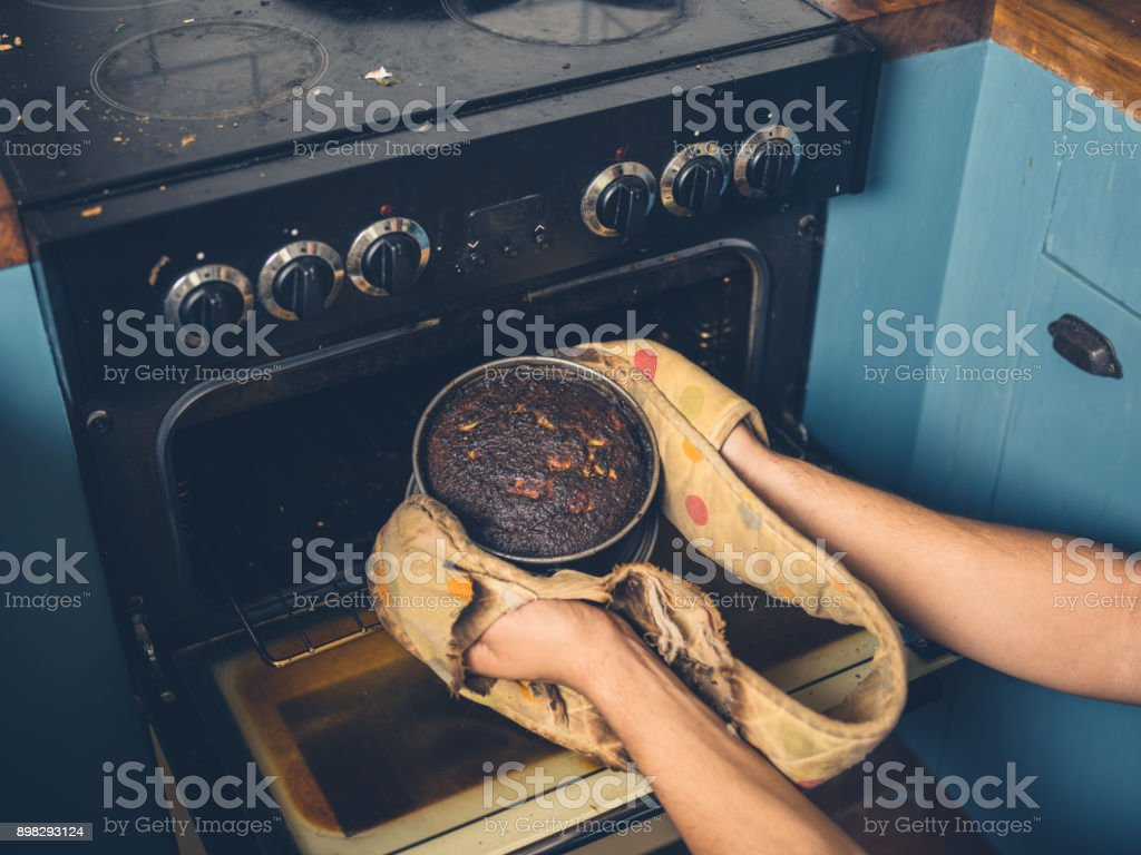Man removing burnt cake from the oven The hands of a man is removing a burnt cake from the oven Adult Stock Photo