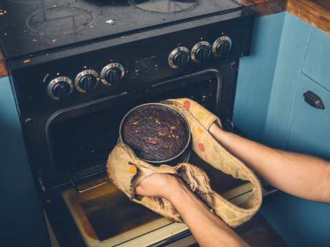 Man Removing Burnt Cake From The Oven Stock Photo - Download Image Now