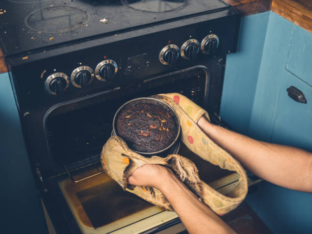 Man removing burnt cake from the oven stock photo
