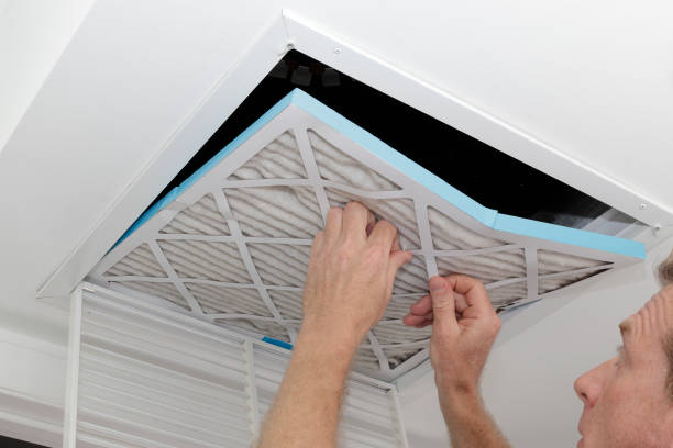 Man Removing Dirty Air Filter Person removing an old dirty air filter from a ceiling intake vent of a home HVAC system. Unclean gray square furnace air filter being taken out of a ceiling air vent. air filter stock pictures, royalty-free photos & images