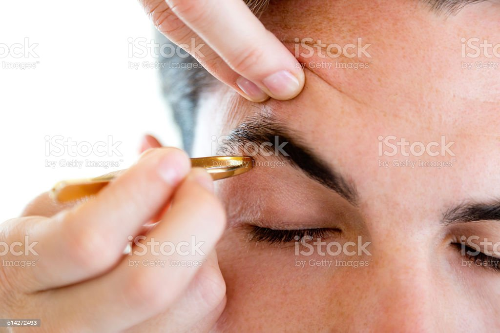 Man removing eyebrow hairs with tweezing. stock photo
