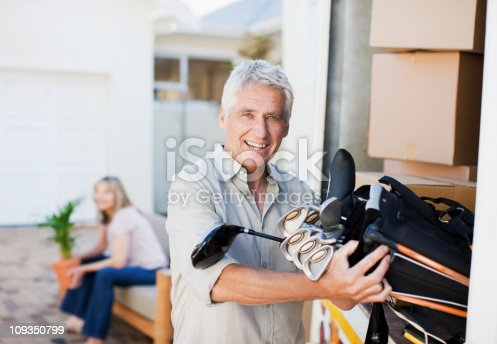 istock Man removing golf clubs from moving van 109350799