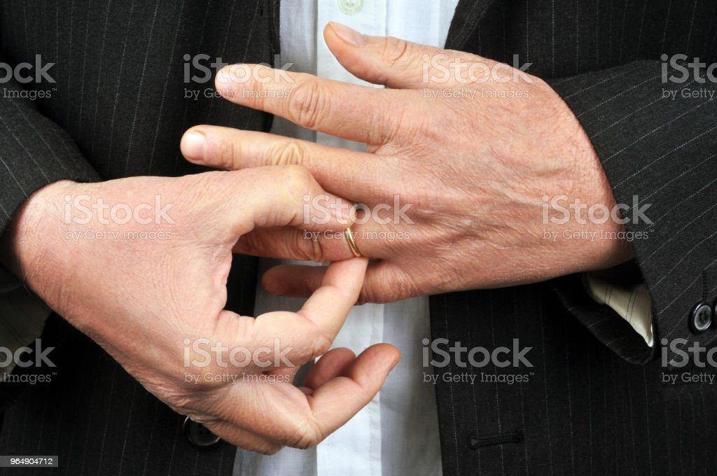 Homme retirant son alliance du doigt royalty-free stock photo