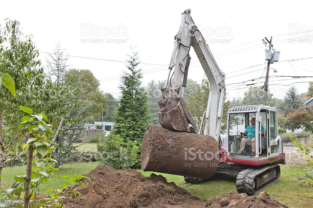 Man removing old oil tank with excavator stock photo