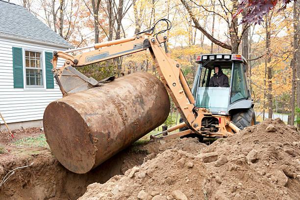 man removing old oil tank with excavator - brandstoftank stockfoto's en -beelden