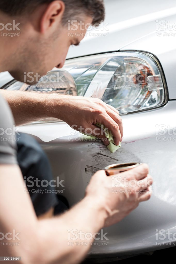 Man removing scratches from car bumper stock photo