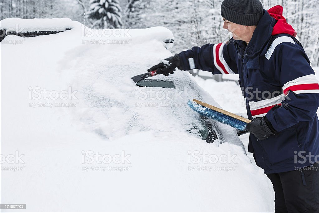 Man removing snow from windshield with ice scraper royalty-free stock photo