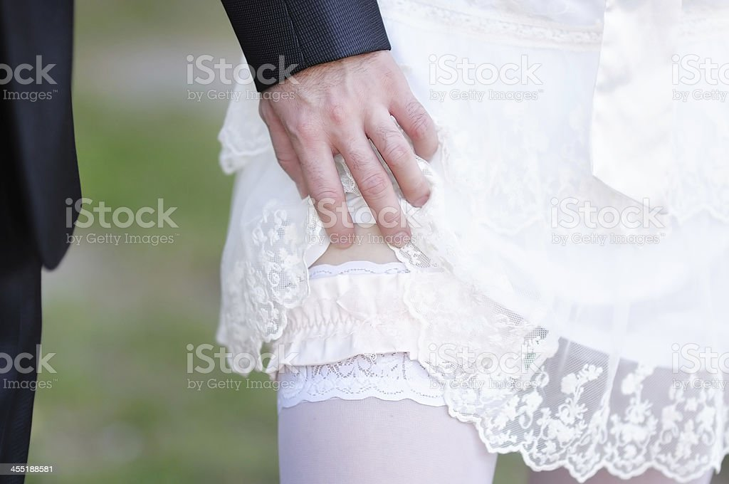 Man removing the garter from a newly married woman stock photo