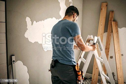 891274328 istock photo Man renovating his apartment 1169730780