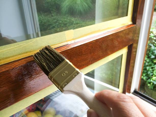 Man repaint a window frame Man repaint a window frame with brown varnish lacquered stock pictures, royalty-free photos & images