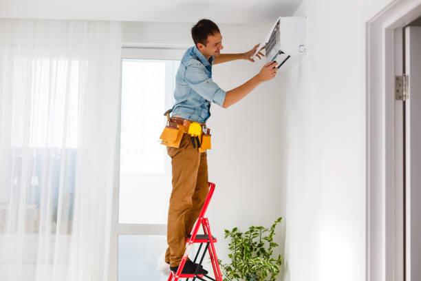 man repair air conditioner stock photo