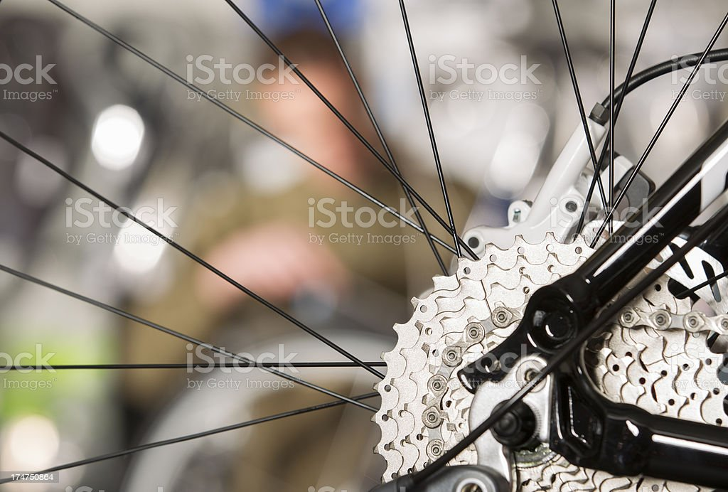 Man repairing a bicycle in small shop royalty-free stock photo