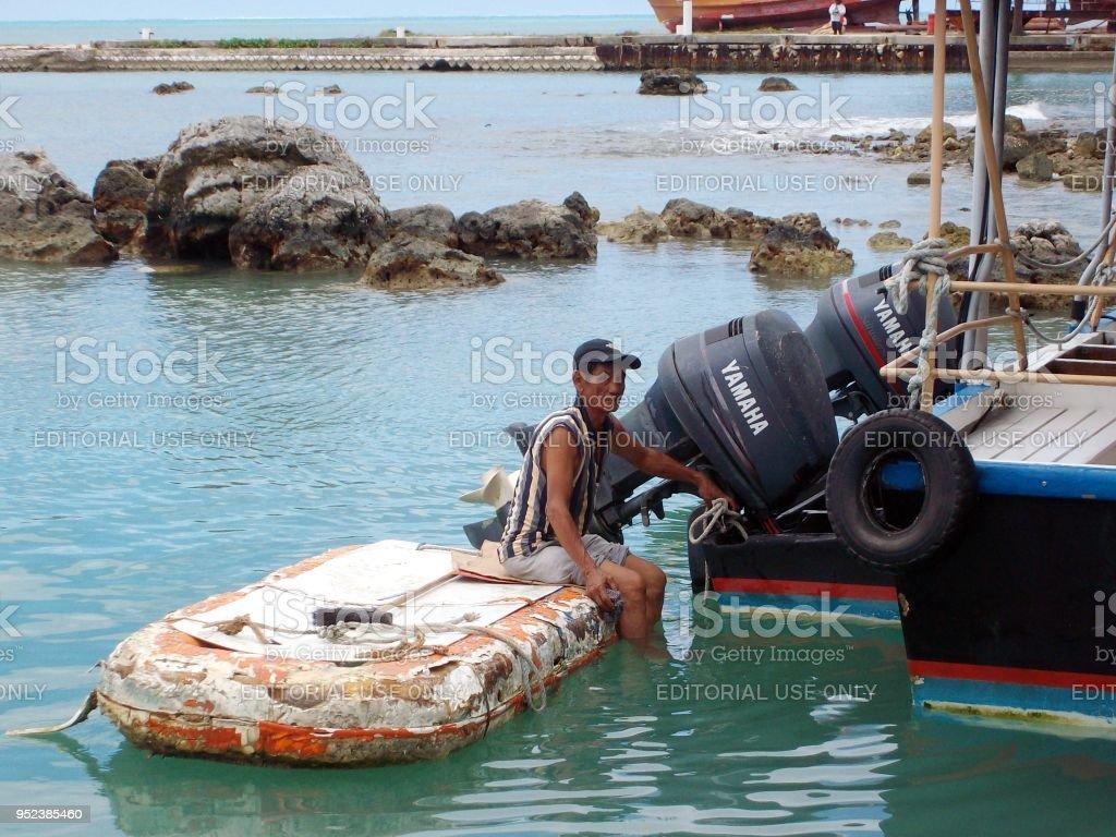 man repairing a boat at the Smiling Cove Marina in Saipan stock photo