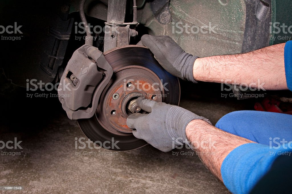 Man repairing a brakes stock photo