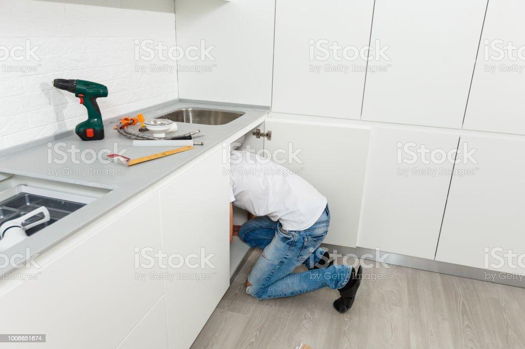 Hombre reparar fregadero de la cocina en casa - foto de stock