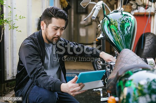 Man streaming online tutorials to repair a motorcycle